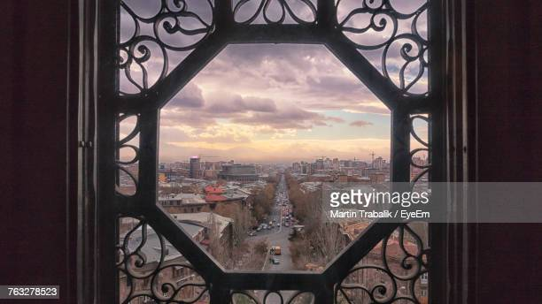 View Of Cityscape Through Window During Sunset