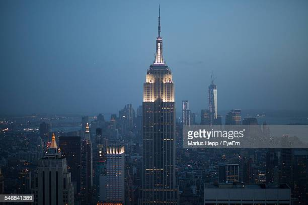 view of cityscape with empire state building at night - empire state building stock pictures, royalty-free photos & images