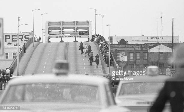 View of Civil Rights marchers as they walk back over the Edmund Pettus Bridge after being stopped by police violence during the first Selma to...