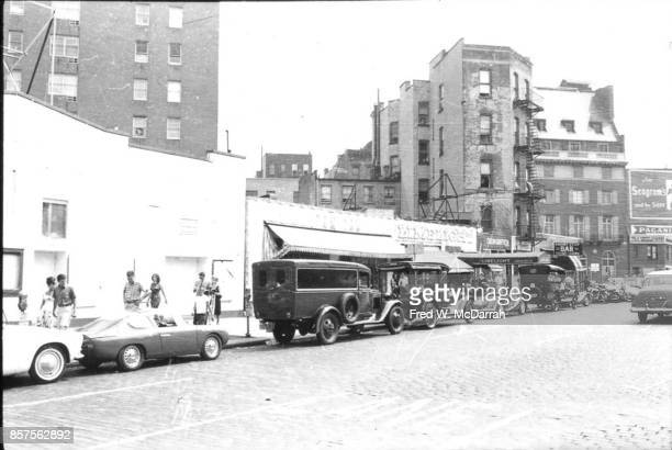 View of classic cars parked in front of the Limelight Coffee House during the seventh annual Village Voice Auto Rallye New York New York July 28 1963