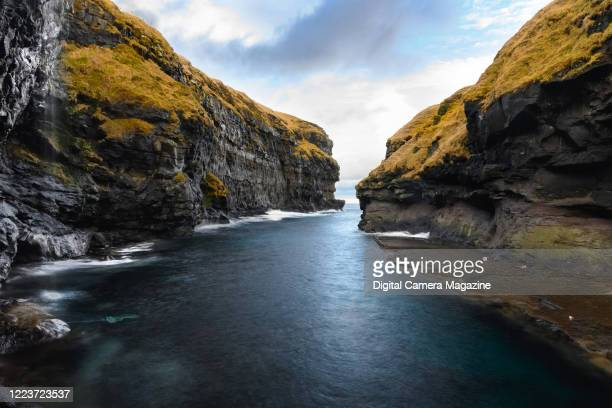 View of cliffs surrounding a natural harbour near the village of Gjogv in the Faeroe Islands, on February 21, 2019.