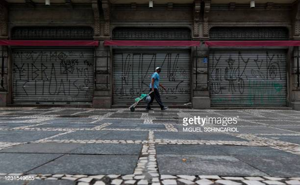 View of closed stores and empty streets after non-essential services were shut down at midnight and until March 20 in the state of Sao Paulo, amid...