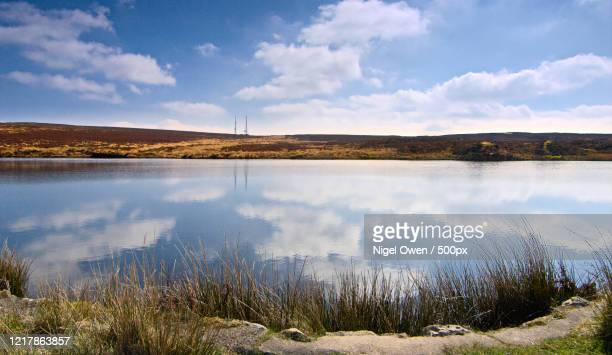 view of clouds reflected in pond, keepers pond, wales, uk - nigel owen stock pictures, royalty-free photos & images