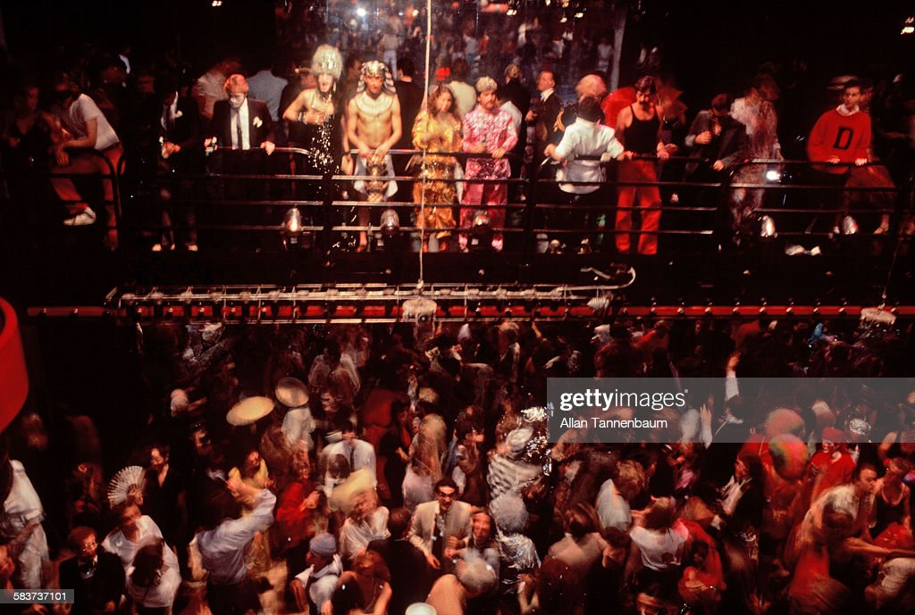 View of clubgoers, a number of them in costume, observe the dance from a newly constructed bridge at Studio 54, New York, New York, May 9, 1978.