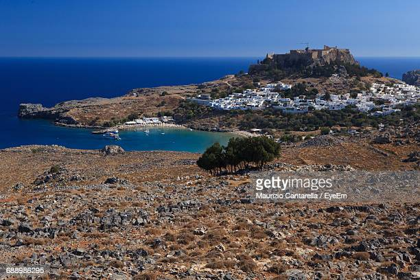 view of coastal town and boats in lindos bay, greece - dodecanese islands stock photos and pictures