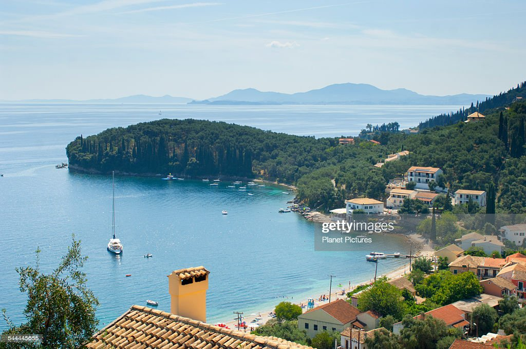 View of coastal village rooftops and bay, Corfu, Greece : Stock Photo