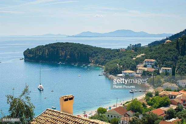 View of coastal village rooftops and bay, Corfu, Greece