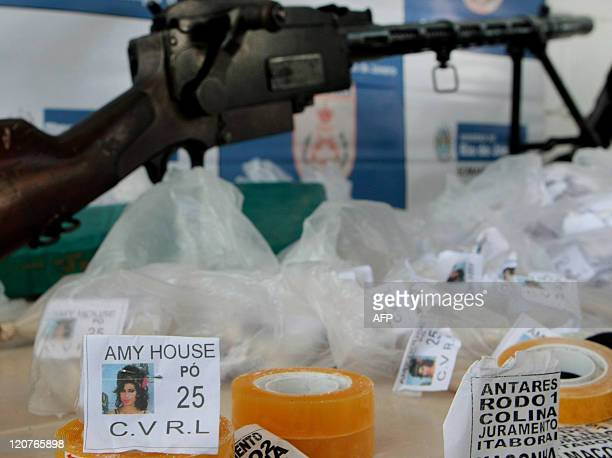 View of cocaine doses in plastic bags with a picture of the late English singer Amy Winehouse seized during a raid on Mandela shantytown on August 9...