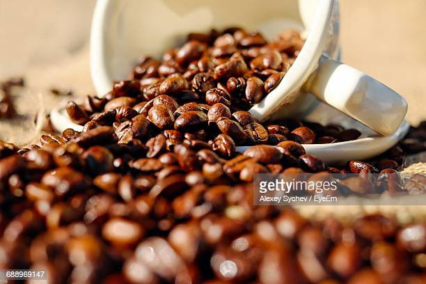 View Of Coffee Beans Spilling From Cup