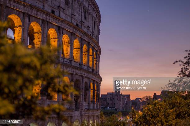 view of coliseum against sky during sunset - colosseo foto e immagini stock