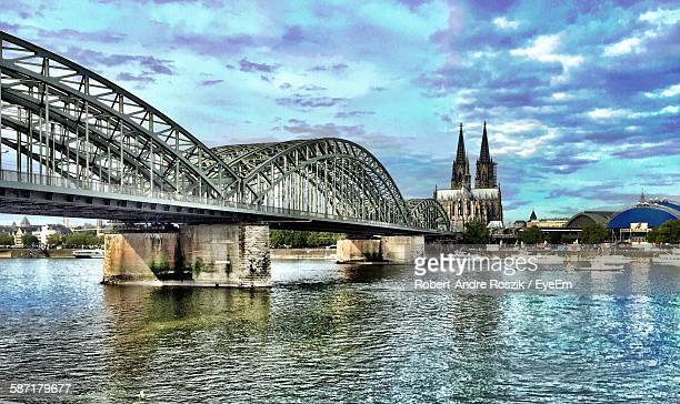View Of Cologne Cathedral With Hohenzollern Bridge Over Rhine River Against Sky