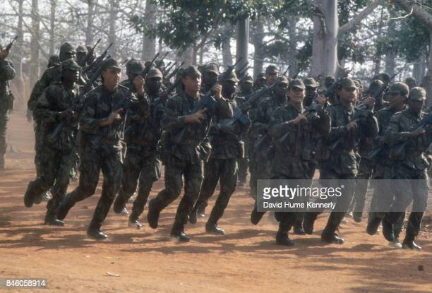 View of Colonial Portuguese soldiers with their rifles run along a dirt road during training Ancuabe Cabo Delgado Province Mozambique July 27 1973...