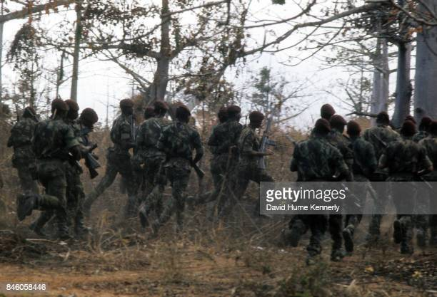 View of Colonial Portuguese soldiers with their rifles run through the brush during training Ancuabe Cabo Delgado Province Mozambique July 27 1973...