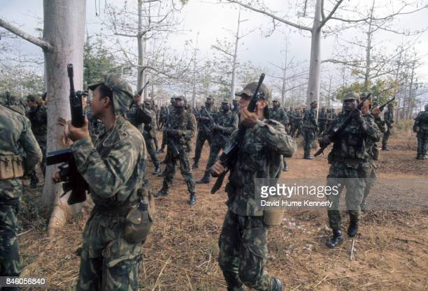 View of Colonial Portuguese soldiers with their rifles stand among trees during training Ancuabe Cabo Delgado Province Mozambique July 27 1973 The...