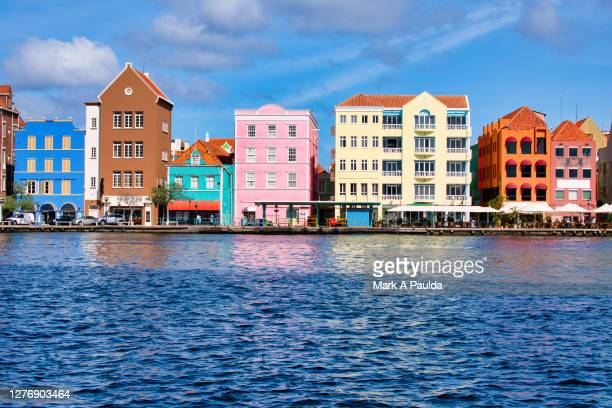 view of colorful buildings in curacao across the water - curaçao stockfoto's en -beelden