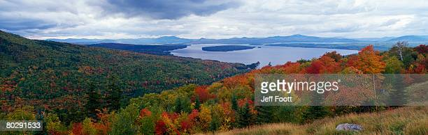 view of colorful fall foliage and approaching storm clouds from scenic overlook called height of land. height of land, mooselookmeguntic lake, maine, north america. - mooselookmeguntic lake stock photos and pictures
