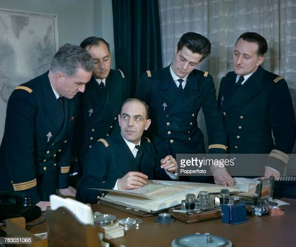 View of Commander of the Free French naval forces Admiral Philippe Auboyneau pictured seated at a desk with Free French officers stationed in Britain...