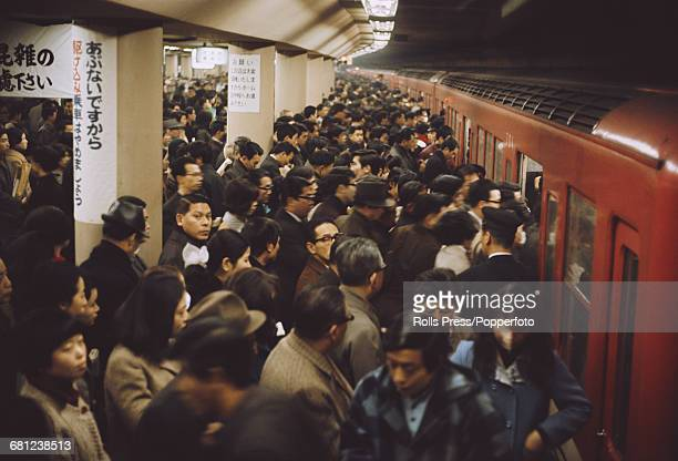 View of commuters and residents attempting to enter a metro subway train during rush hour at Shinjuku Station in Tokyo Japan in 1970