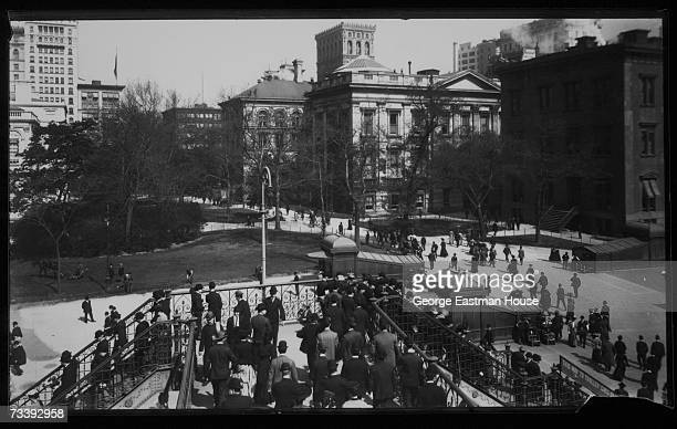 View of commuters as they enter and leave the elevated railroad station at City Hall Square and Park in downtown Manhattan New York New York early...