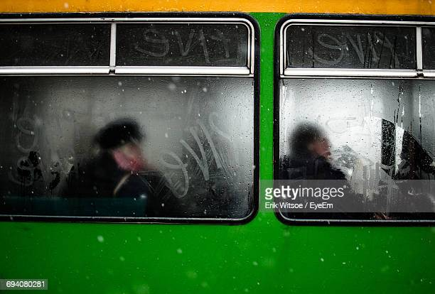 view of commuters through train window - train graffiti stock photos and pictures