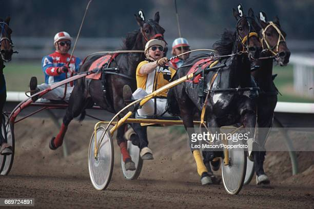 View of competition in a harness racing event with horses trotting as they pull drivers on sulky carts around the track at Hollywood Park Racetrack...