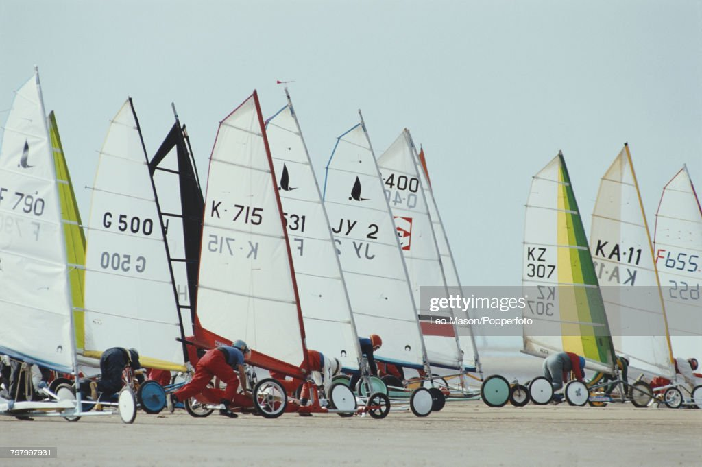 View of competitors lining up their sand yachts in position prior to competing in the land sailing (land yachting) World Championships on Blackpool Beach, England in 1987.