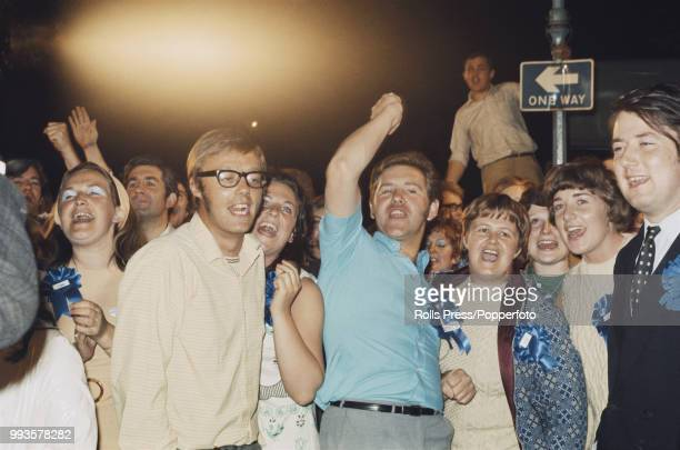 View of Conservative Party supporters some wearing Tory and Heath blue rosettes cheer and shout after hearing of Edward Heath's victory in his Bexley...