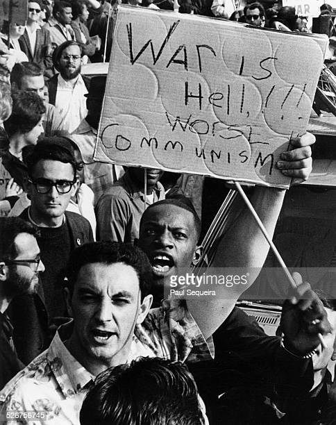Man holds a sign that reads 'War Is Hell!!! Worse is Communism,' as he participates in an anti-protest against the marchers participating in the...