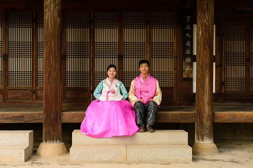 View of couple wearing Korean traditional clothes and sitting on a wooden porch - gettyimageskorea