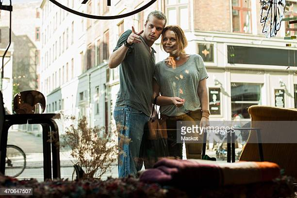 View of couple window shopping from store