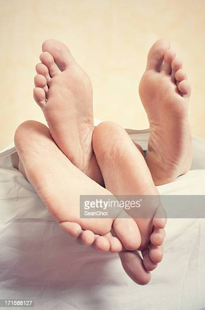 View of couple's bare feet as they are under bed sheet.