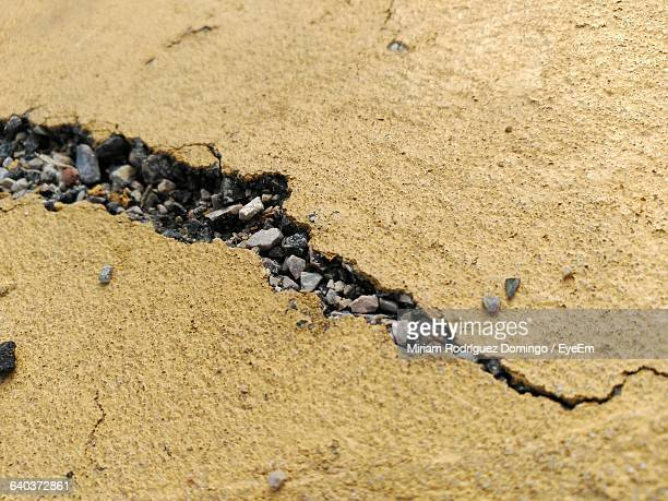 view of cracked concrete road and gravel on road surface - earthquake stock pictures, royalty-free photos & images