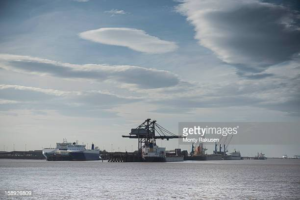 View of cranes and ships at sea with clouds in sky