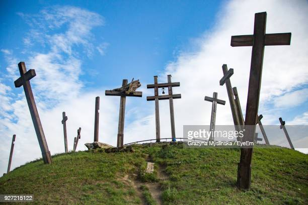 View Of Cross On Landscape Against Blue Sky