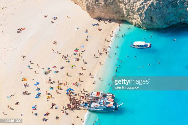 view of crowded navagio beach on zakynthos - crowded beach stock pictures, royalty-free photos & images