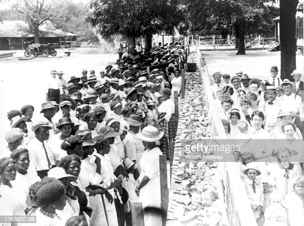 View of crowds at an annual barbecue given on the plantation of FM Gay, Alabama, 1930s. The crowds are segregated.