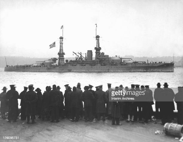 View of crowds gathered at the 96th Street Pier to watch the USS Arizona leading the fleet in a naval review for Secretary of the Navy Josephus...