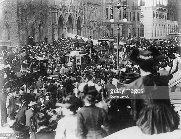 A view of crowds of people gathered on Fifth Avenue outside a church for a wedding between the Roxborough and Goelet families New York City Men ride...
