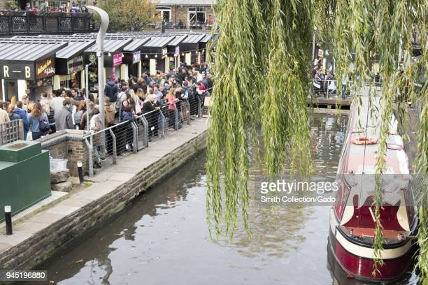 View of crowds of shoppers, walking around the canal, with a red and cream canal boat docked at right, and the leaves of a willow tree in the right...