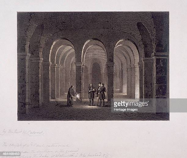 View of crypt in St Paul's Cathedral London with a figure showing three men the Duke of Wellington's probable burial place indicated by the light...