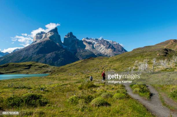 View of Cuernos del Paine Mountains from Salto Grande trail with hikers in Torres del Paine National Park in southern Chile