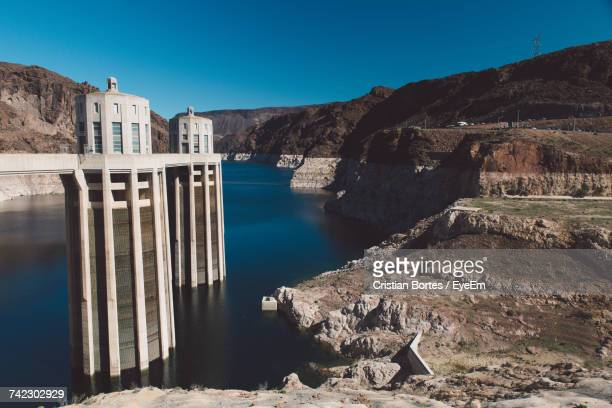 view of dam on riverbank - bortes stockfoto's en -beelden