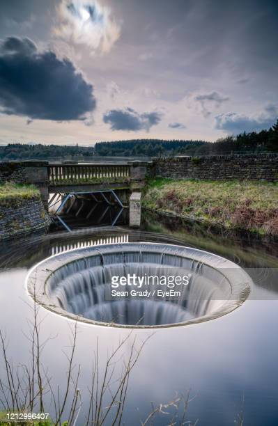 view of dam overflow against a sky. - reservoir stock pictures, royalty-free photos & images