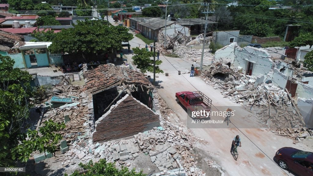 TOPSHOT - View of damages after the 8.2 magnitude earthquake that hit Mexico's Pacific coast, in Ixtaltepec, state of Oaxaca on September 9, 2017. Police, soldiers and emergency workers raced to rescue survivors from the ruins of Mexico's most powerful earthquake in a century, which killed at least 61 people. /