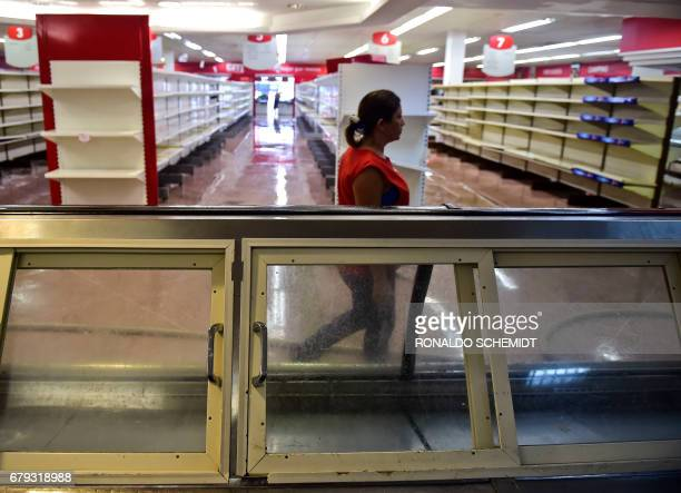 View of damages in a supermarket in Valencia Carabobo State on May 5 the day after antigovernment protesters looted stores set fire to cars and...