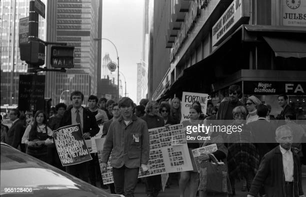 View of demonstrators among pedestrians as they cross 49th Street on 6th Avenue during the Moratorium to End the War in Vietnam demonstration New...