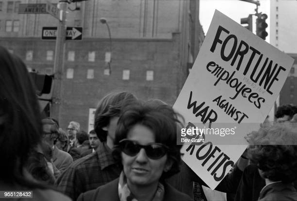 View of demonstrators among pedestrians as they cross 6th Avenue on West 42nd Street during the Moratorium to End the War in Vietnam demonstration...
