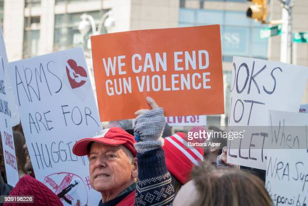 View of demonstrators, many with signs, as they participate in the March For Our Lives rally against gun violence, near Columbus Circle, New York,...