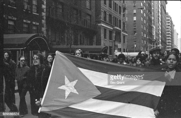 View of demonstrators two of whom hold a Puerto Rican flag as they march on a street New York New York December 1969 Among those pictured is the...