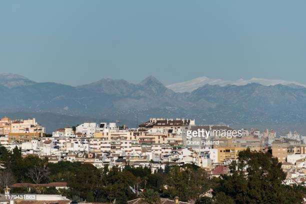 view of densely constructed coast of costa del sol in the afternoon sun with the sierra nevada with snow in the background - dorte fjalland fotografías e imágenes de stock